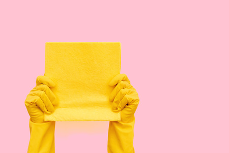 Woman in bright yellow latex rubber gloves holding cleaning towel in her hands isolated on pastel pink background with empty space for text Stock Photo