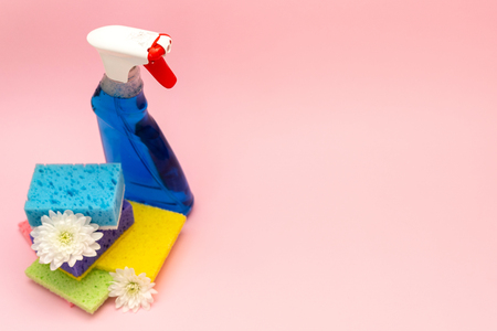 High angle top view bottle of detergent spray for windows and glass standing near some sponges with flowers, isolated on pastel pink background with empty space for text