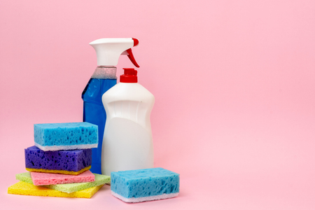 Two bottle of detergent soap and spray for windows and glass  standing near sponges isolated on pastel pink background with empty space for text