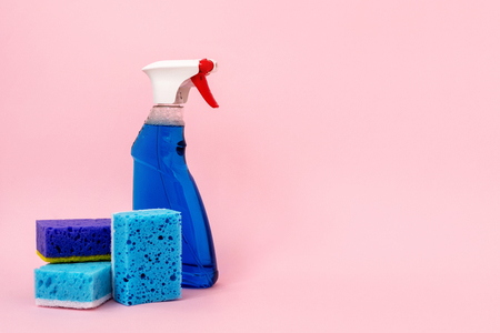 Photo of bottle of detergent spray for windows and glass standing near blue sponges isolated on pastel pink background with empty space for text Imagens