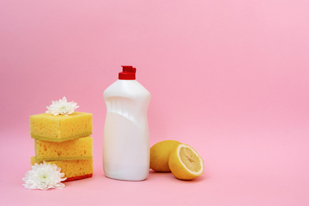 White bottle of cleaning dish soap standing near some yellow sponges, lemons and flowers isolated on pastel pink background Banco de Imagens
