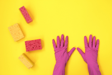 Woman holding two hand in pink rubber gloves near some washing sponge isolated on yellow background