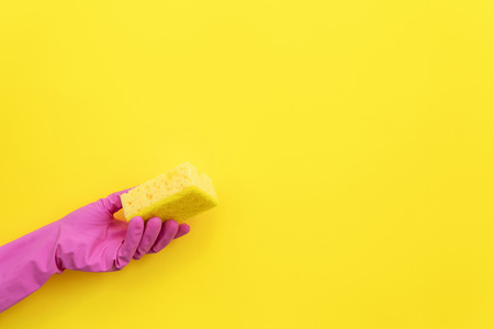 Woman holding polyurethane dish sponges for washing in hand isolated on yellow background with empty space for text