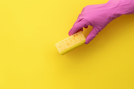 Woman holding sponges for washing in hand isolated on yellow background with empty space for text Imagens