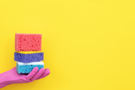 Woman holding stack of some polyurethane dish sponges for washing on her hand isolated on yellow background with empty space for text Imagens