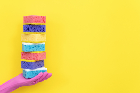 Woman in pink rubber gloves holding stack of different polyurethane dish sponges for washing on palm hand isolated on yellow background with empty space for text Imagens