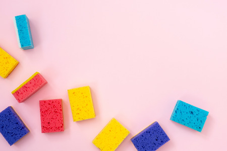 Colorful polyurethane dish sponges for washing laying isolated on pastel pink background with empty space for text Imagens