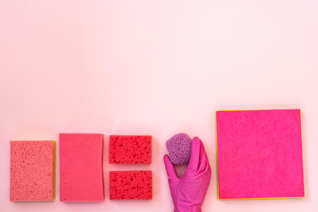 Hand holding scrub near pink polyurethane dish sponges for washing. They laying isolated on pastel background with empty space for text