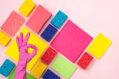 Woman hand give ok-sign and thumbs up against cleaning items isolated on pastel pink background
