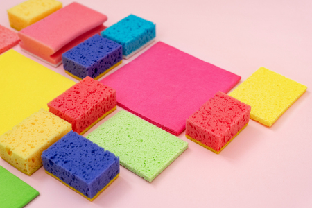 Group of colorful polyurethane dish sponges and other cleaning stuff isolated on pastel pink background Banco de Imagens