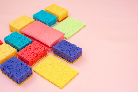 Side view photo of colorful sponges lying isolated on pastel pink background with empty space for text Banco de Imagens