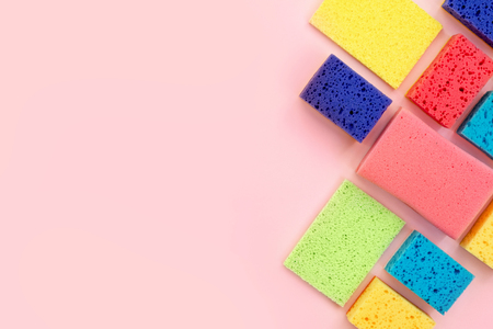 High angle top view photo of colorful sponges isolated on pastel pink background with empty space for text