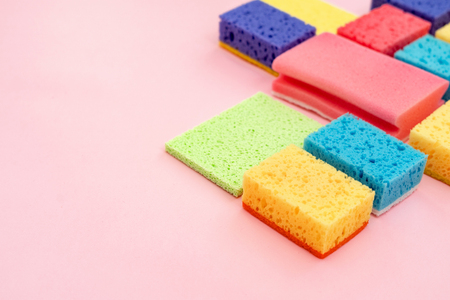 Some colorful polyurethane dish sponges and other cleaning stuff isolated on pastel pink background with empty space for text