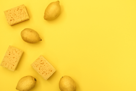 Sponge for dishes washing and some lemons lying isolated on bright yellow background with empty space for text
