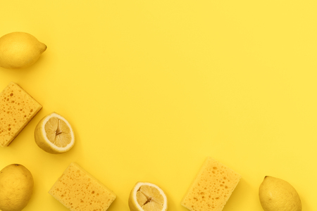 Some sponge for dishes washing and lemons lying isolated on yellow background with empty space for text