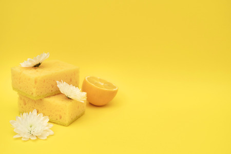 Stack pf sponge for dishes washing, lemons and white flowers lying isolated on yellow background with empty space for text