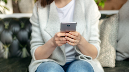 Cropped and close up photo of lady in trendy wear sitting inside loft interior space in restaurant. She holding portable telephone equipment in her hands Imagens