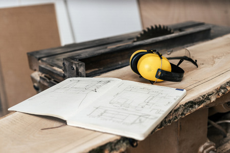 Hobby wood concept. Photo of white notebook with technical drawing lying on top of wood plank board in garage or workroom near table saw focus on yellow headset