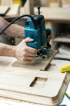 Hobby wood concept. Vertical cropped photo of cabinetmaker handcraft hands hold tool plunge it in wood make furniture in garage or workroom