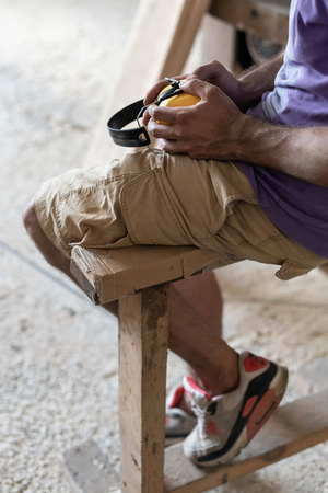 Manual wood concept. Profile side view cropped photo of cabinetmaker handyman sit in garage or workroom on a bench in sneakers hold headset in hands