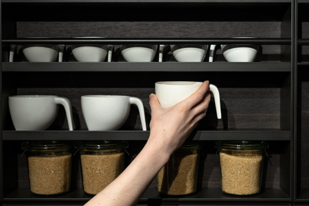 Woman holding in hand white tea or coffee ceramics cup against black kitchen wood shelf with design component Banque d'images