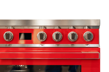 Element of red cooking stove with stainless steel switches on hob standing in modern kitchen Stock Photo