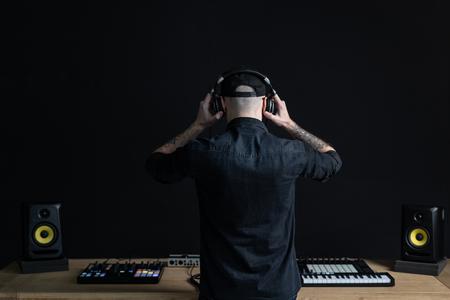 Hinten zurück hinter der Ansicht eines nicht erkennbaren professionellen DJ-Mannes mit Headset. Er ist bereit oder bereitet sich auf kreative Musik im Hausraumstudio mit schwarzem dunklem Wandinterieur vor Standard-Bild