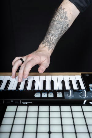 Vertical and cropped photo tattoo hands of disc jockey master. Man using mini piano keyboard and creative music in sound recording studio