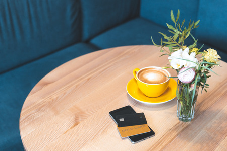 High angle above top view or overhead, flat lay photo of smartphone gadget with credit card lying on wooden table in cafe with bright light and modern interior