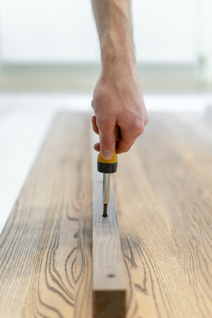 Vertical and close up photo of carpenter person using screwdriver tool and repairing, fixing on building new wooden desk or table top