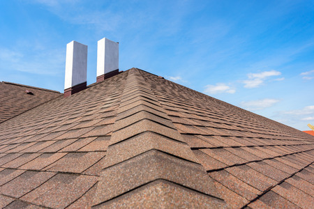 Photo of new roof with asphalt tile and two white chimney on new home under construction, against blue sky