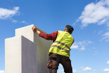 Unrecognizable and mature man measuring white chimney on roof top of new house under construction against beautiful sky background Zdjęcie Seryjne