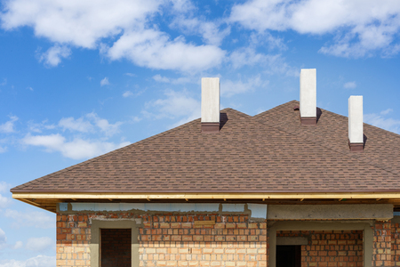 Asphalt tile roof with three white and new chimney on install on residential house under construction against blue background