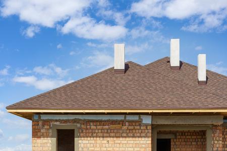 Techo de tejas de asfalto con tres chimeneas blancas y nuevas en instalar en casa residencial en construcción contra el fondo azul.