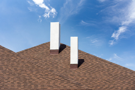 Close up photo of asphalt shingles or tiles installed on top of the new residential house under construction with two white chimneys, against blue sky background