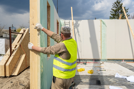 Process of construction new and modern modular house from composite sip panels. Workman in special protective uniform wear working on building development industry of energy efficient property