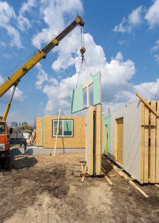 Process of construction new and modern modular house from composite sip panels. Vertical photo of crane with wall against blue background sky
