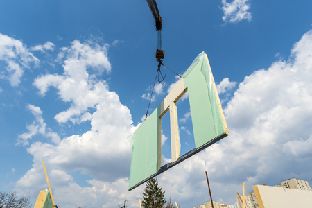 Process of construction new and modern modular house from composite sip panels. Low view angle photo of crane with sip panel against sky and blue background