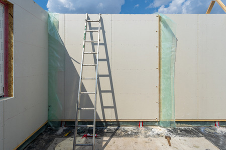 Construction new and modern modular house from composite sip panels. Metal ladder standing by the wall in empty room