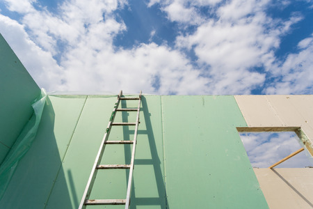 Construction new and modern modular house from composite sip panels. Low angle view photo of metal ladder standing by the wall against beautiful sky background