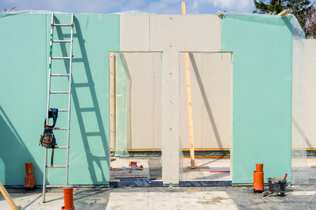 Construction new and modern modular house from composite sip panels. Tool belt with instrument on metal ladder by the wall in unfinished building room Stock Photo