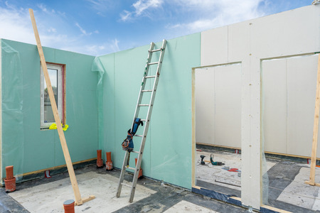Construction new and modern modular house from composite sip panels. Tool belt with instrument on metal ladder by the wall inside unfinished room