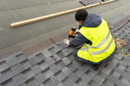 Trabajador calificado en ropa de trabajo uniforme usando pistola de clavos neumática o neumática e instalando tejas de asfalto o betún en la parte superior del nuevo techo en construcción del edificio residencial