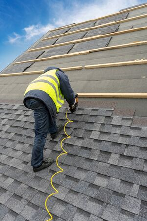 Vertical photo of unrecognizable roofer worker in uniform work wear using air or pneumatic nail gun and installing asphalt or bitumen tile on top of the roof under construction house 写真素材 - 136841100