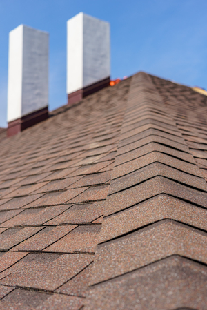 Vertical photo of asphalt tile roof with two white and concrete chimney on new home under construction against blue sky on background Stockfoto