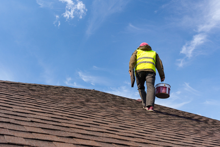 Unrecognizable and skilled workman in uniform standing on tile roof of new home under construction with equipment and instrument