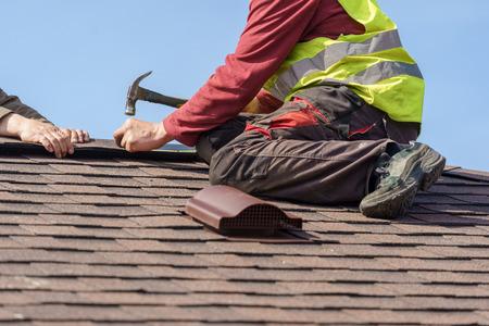 Concepto de proceso de construcción. Dos techadores expertos en ropa de trabajo especial con casco en las manos instalando tejas de asfalto o tejas en la parte superior de la casa nueva