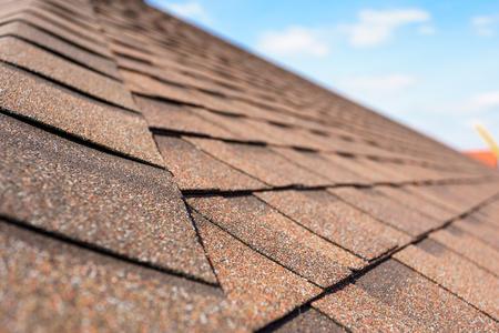 Cerrar y foto de enfoque selectivo de tejas o tejas de asfalto en el techo de la nueva casa en construcción contra el cielo azul Foto de archivo