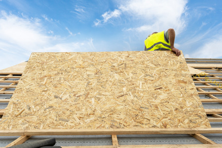Concept of renovation, repair, fixing frame work house. Professional, unrecognizable and qualified roofer standing working on rooftop under construction, holding in hands wooden, plywood or osb panel