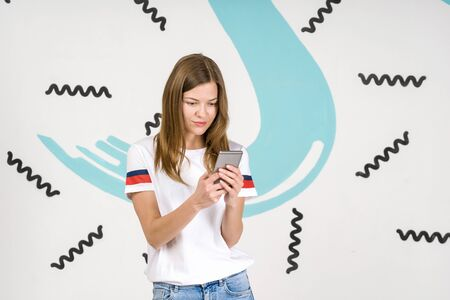 Young beautiful woman standing on white art background with smartphone in hands, texting message